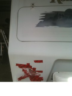 A large hole (indicated by red tape) in a Komfort travel trailer.